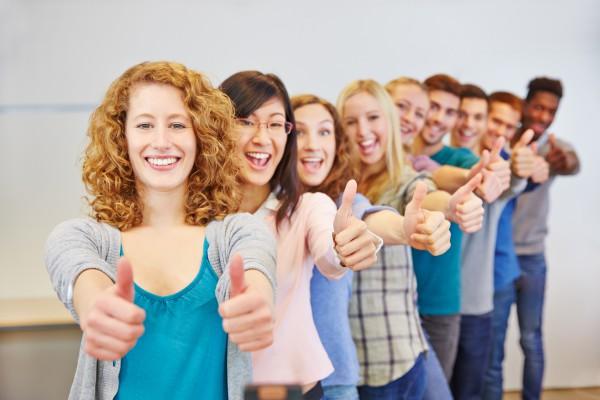 Viele Teenager hintereinander halten ihre Daumen hoch zum Gratulieren